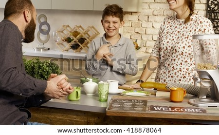 Happy schoolboy having breakfast with parents in the kitchen.