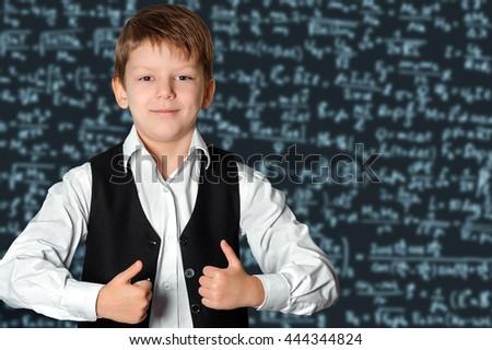 Happy schoolboy  in front of a  blackboard showing thumbs up sign.  Education and school concept - stock photo