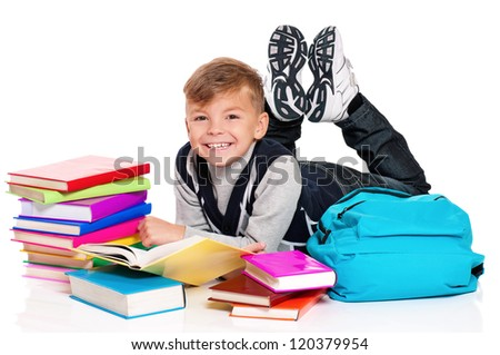 Happy schoolboy lying on floor with backpack and books isolated on white background