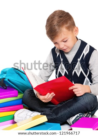 Happy schoolboy sitting on floor with books on white background