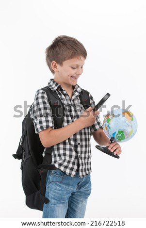 Happy schoolboy wearing backpack and holding magnifying lens. cute schoolboy holding globe on white background - stock photo