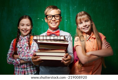 Happy schoolboy with stack of books and two girls standing by the blackboard and looking at camera - stock photo