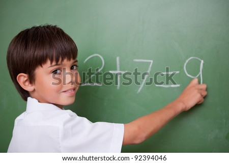 Happy schoolboy writing an addition on a chalkboard - stock photo