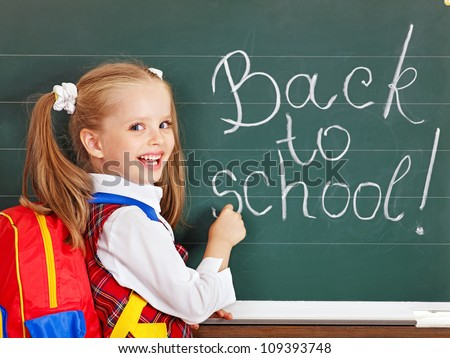 Happy schoolchild writting on blackboard. - stock photo