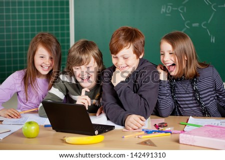 Happy schoolchildren at a classroom during the lesson with laptop