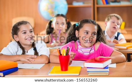 Happy schoolchildren during lesson in classroom at school - stock photo