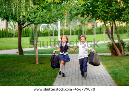 happy schoolchildren running in the park after school. waving backpacks. September 1