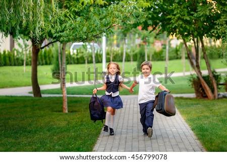happy schoolchildren running in the park after school. waving backpacks. September 1 - stock photo
