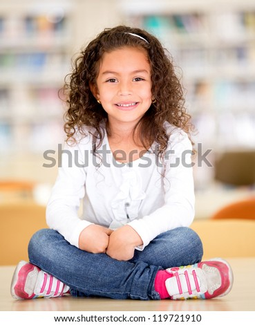 Happy schoolgirl at the library sitting on top of a table - stock photo