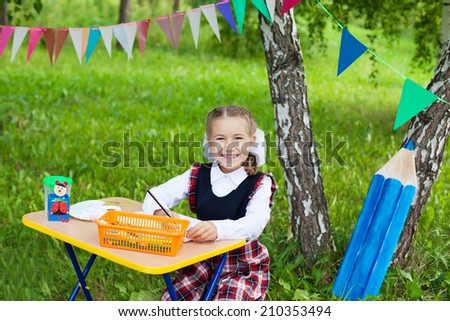 Happy schoolgirl child kid girl sitting at table and writing, classroom outdoors, back to school - stock photo