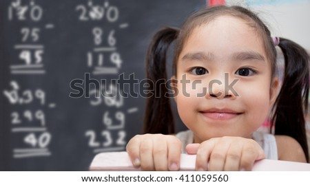 happy schoolgirl , childhood and education concept - happy little girl with chalk drawing Mathematical calculations on blackboard - stock photo