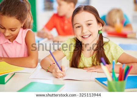 Happy schoolgirl looking at camera at drawing lesson - stock photo