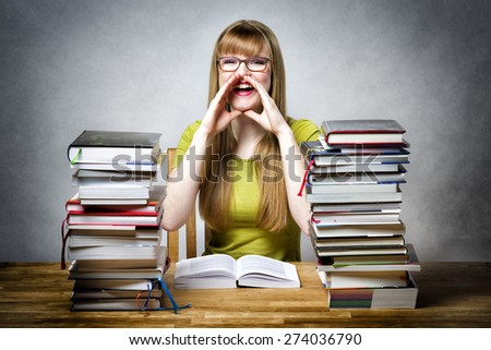 Happy schoolgirl sitting at desk with books, holding his hands to his mouth and calls something - stock photo