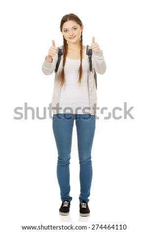 Happy schoolgirl with backpack and thumbs up. - stock photo