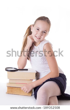 Happy schoolgirl with pile of books isolated on white - stock photo