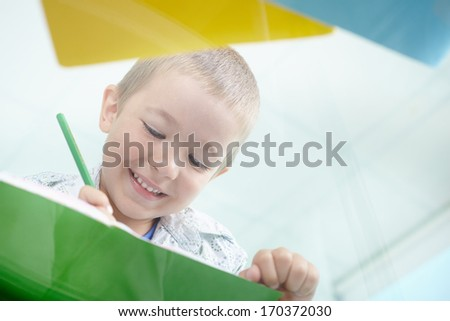 Happy schoolkid drawing with green pencil - stock photo