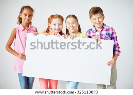Happy schoolkids holding blank paper and looking at camera