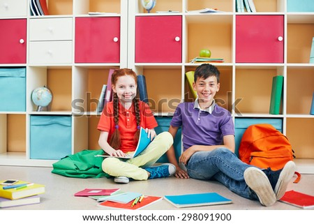 Happy schoolmates looking at camera while sitting on the floor during break - stock photo