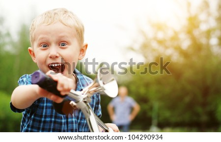Happy screaming boy riding by bicycle - stock photo