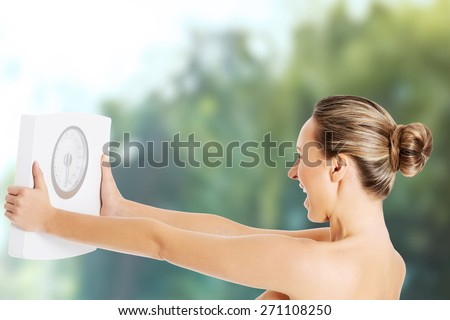 Happy screaming woman holding a scale. - stock photo