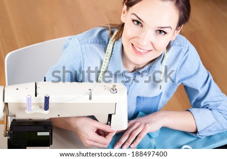 Happy seamstress sewing clothes at her studio - stock photo