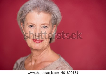 Happy seior woman in front of red background