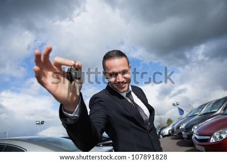 Happy seller holding car keys outdoors - stock photo