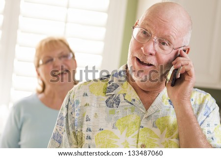 Happy Senior Adult Husband on Cell Phone with Wife Behind in Kitchen. - stock photo