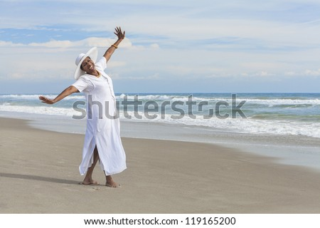 Happy senior African American woman dancing alone on a deserted tropical beach - stock photo
