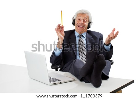 Happy senior business man in dark suit sits with feet up on desk, wears headphones, waves pencil, gets ideas. Isolated on white, horizontal, copy space.
