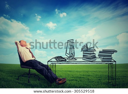 Happy senior businessman relaxing at his desk in the middle of green meadow outdoors - stock photo