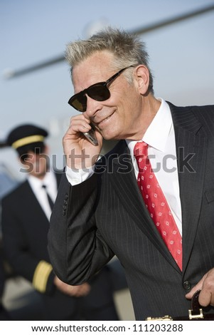 Happy senior businessman using cell phone with airplane captain in the background at airfield