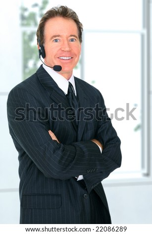 happy senior businessman wearing headset while working in his office