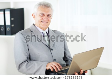 Happy Senior businessman working at home on laptop.