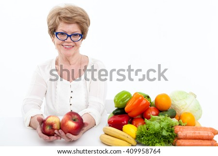 Happy senior Caucasian woman stretching hands with two big red apple, vegetables and fruits are on table, white background - stock photo
