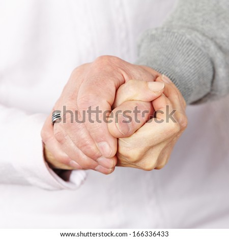 Happy senior citizen couple holding their hands together