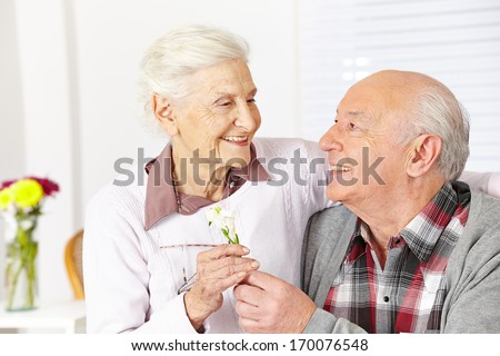 Happy senior citizen giving a freesia flower to smiling woman - stock photo