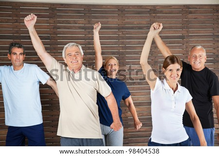 Happy senior citizens dancing to fitness music in gym - stock photo