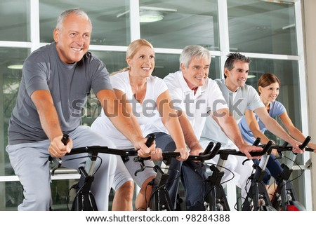 Happy senior citizens exercising in class in fitness center - stock photo
