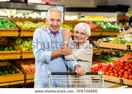 Happy senior couple at the grocery shop looking at the camera - stock photo