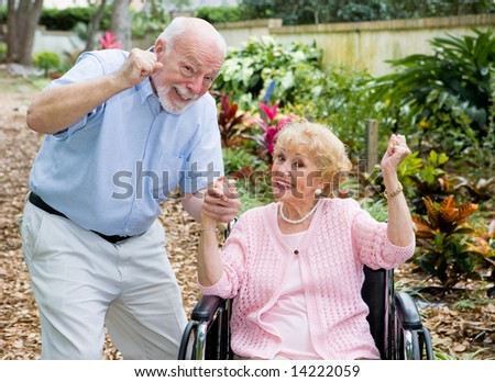 Happy senior couple conquering the challenge of her disability together. - stock photo