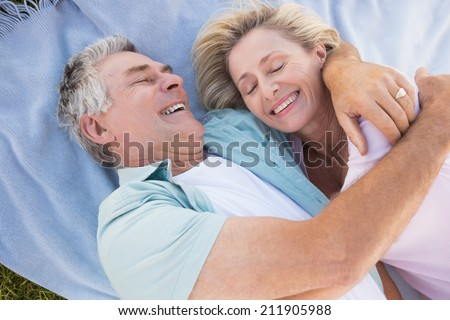Happy senior couple cuddling on blanket on a sunny day