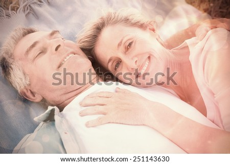 Happy senior couple cuddling on blanket on a sunny day - stock photo