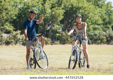 Happy senior couple cycling in the park. Senior man pointing to mature woman the way to choose for a bike trip. Happy cyclist biking in a summer day.