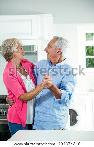 Happy senior couple dancing while standing in kitchen - stock photo
