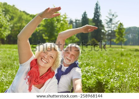 Happy senior couple doing sports together in summer in nature - stock photo