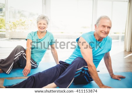 Happy senior couple doing yoga on exercise mat at home - stock photo