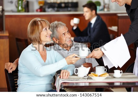 Happy senior couple drinking coffee at coffee shop in hotel - stock photo