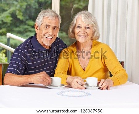 Happy senior couple drinking coffee in a retirement home - stock photo