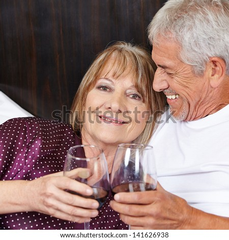 Happy senior couple drinking red wine in bed